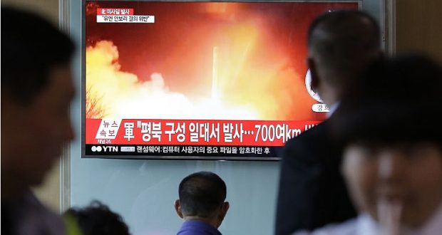 """People watch a TV news program showing a file image of a missile launch conducted by North Korea, at the Seoul Railway Station in Seoul, South Korea, Sunday, May 14, 2017. North Korea on Sunday test-launched a ballistic missile that landed in the Sea of Japan, the South Korean, Japanese and U.S. militaries said. The launch is a direct challenge to the new South Korean president elected four days ago and comes as U.S., Japanese and European navies gather for joint war games in the Pacific. The signs read: """"A missile was fired from near Kusong in North Phyongan province."""" (AP Photo/Ahn Young-joon)"""