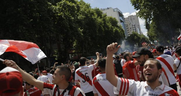 River Plate fans cheer for their team near the stadium in Buenos Aires, Argentina, Saturday, Nov. 24, 2018. Boca Juniors players were injured after their bus was attacked on the way to the Copa Libertadores final against River Plate on Saturday. Boca chairman Daniel Angelici requested the second leg be suspended. (AP Photo/Sebastian Pani)