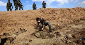 (FILES) In this file photo taken on February 03, 2015 An Iraqi man inspects, the remains of members of the Yazidi minority killed by the Islamic State (IS) jihadist group after Kurdish forces discovered a mass grave near the village of Sinuni, in the northwestern Sinjar area. - The Islamic State group left behind more than 200 mass graves in Iraq containing up to 12,000 victims that could hold vital evidence of war crimes, the UN said November 6, 2018. The United Nations in Iraq (UNAMI) and its human rights office said they had documented a total of 202 mass graves in parts of western and northern Iraq held by IS between 2014 and 2017. (Photo by Safin HAMED / AFP)
