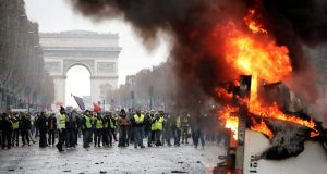 """A truck burns during a """"Yellow vest"""" protest against higher fuel prices during clashes on the Champs-Elysees in Paris, France, November 24, 2018. REUTERS/Benoit Tessier"""