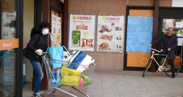 A resident wearing a respiratory mask pushes her cart after shopping in a supermarket on February 23, 2020 in the small Italian town of Casalpusterlengo, under the shadow of a new coronavirus outbreak, as Italy took drastic containment steps as worldwide fears over the epidemic spiralled. (Photo by Miguel MEDINA / AFP)