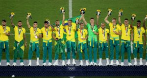 YOKOHAMA, JAPAN - AUGUST 07: Gold medalists of Team Brazil celebrate on the podium during the Men's Football Competition Medal Ceremony on day fifteen of the Tokyo 2020 Olympic Games at International Stadium Yokohama on August 07, 2021 in Yokohama, Kanagawa, Japan. (Photo by Clive Mason/Getty Images)
